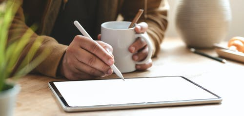 Person Holding White Ceramic Mug While Writing on Tablet