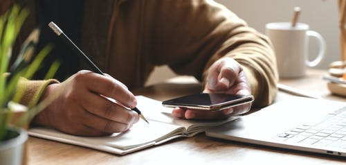 Person Holding Smartphone While Writing
