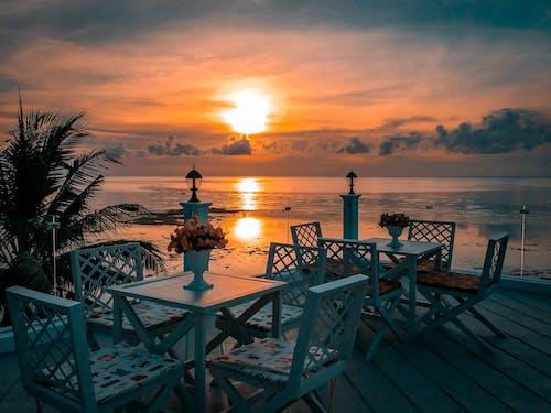 Günbatımı Sırasında Denize Yakın Sandalyeli Beyaz Ahşap Masalar