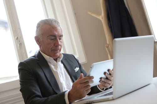 Man in Black Suit Jacket Using Tablet