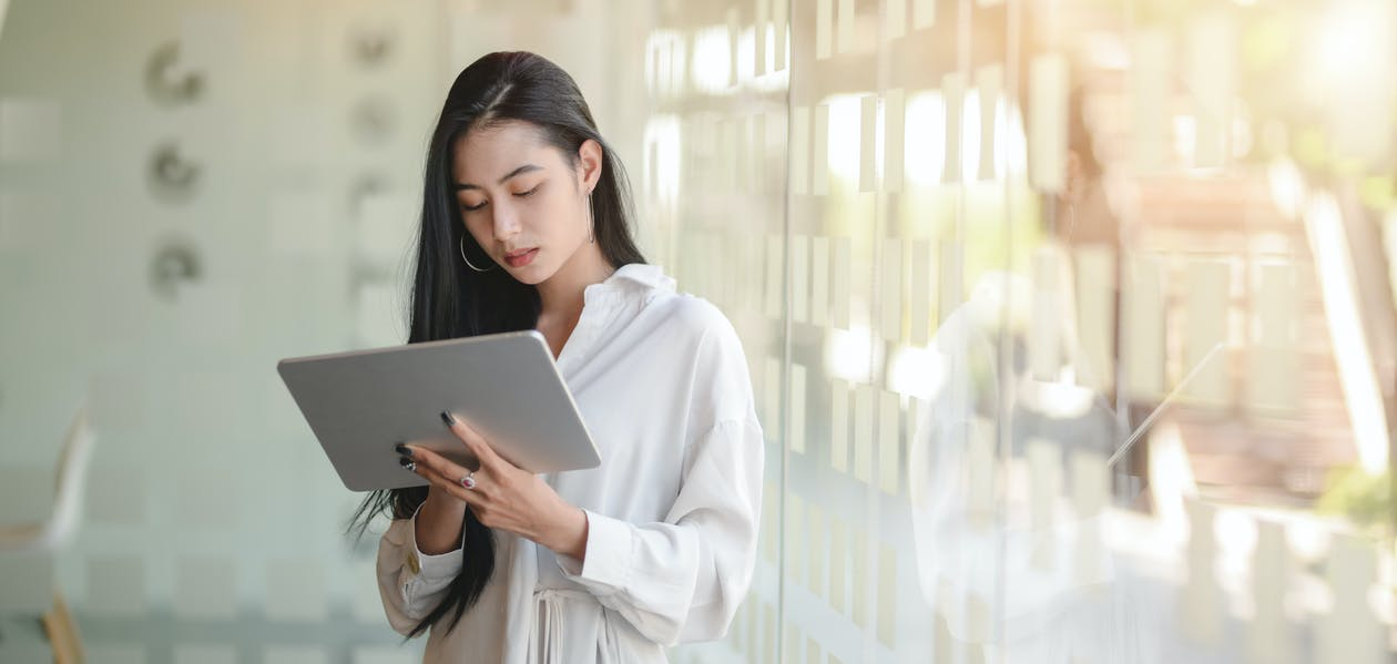 Woman in White Robe Holding White Tablet Computer