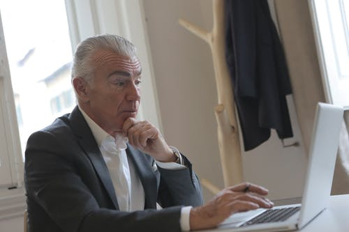 Man in Black Suit Jacket Using Laptop Computer