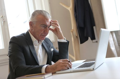 Man in Black Suit Jacket While Using Laptop