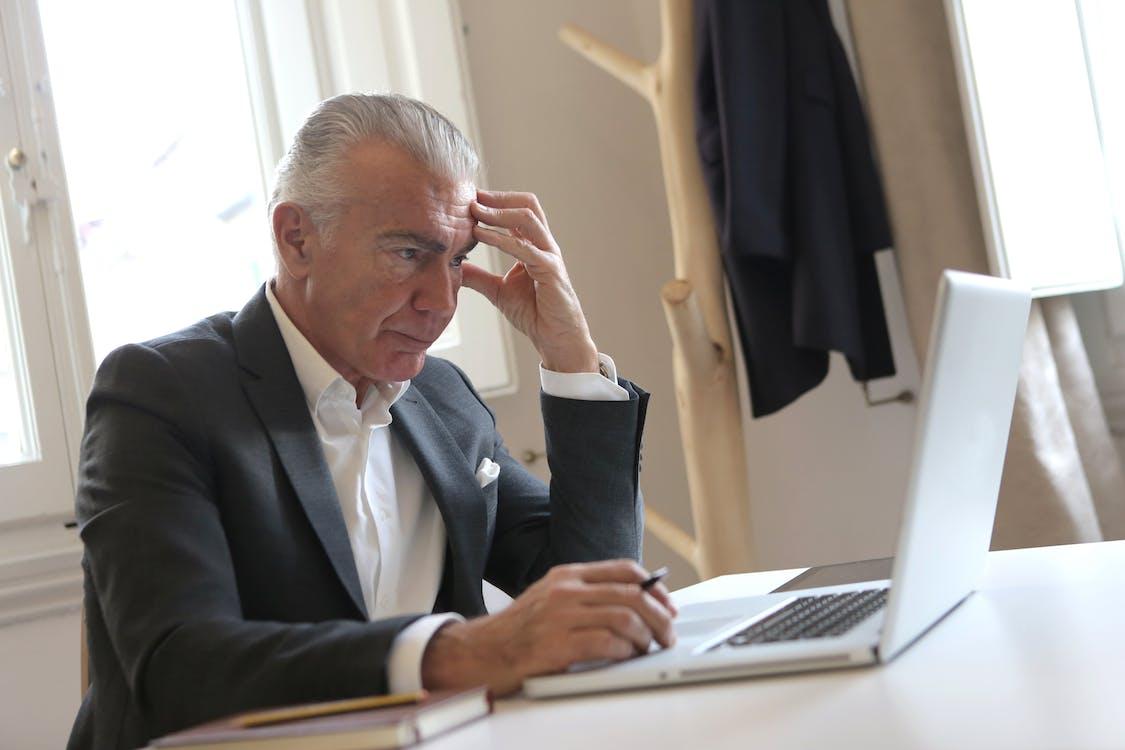 Man in Black Suit Jacket While Using Laptop