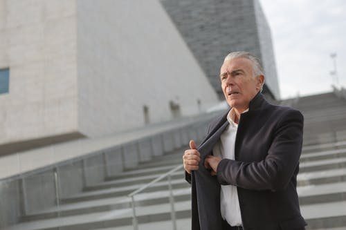 Confident senior businessman standing on stairs in street