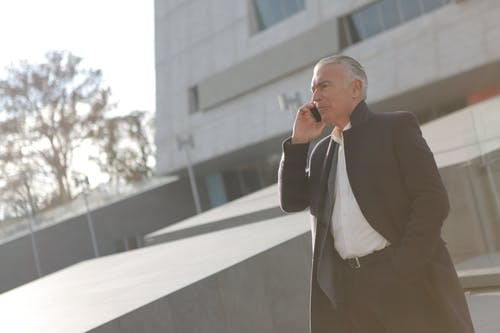 Man in Black Suit Jacket and White Dress Shirt Talking on Phone