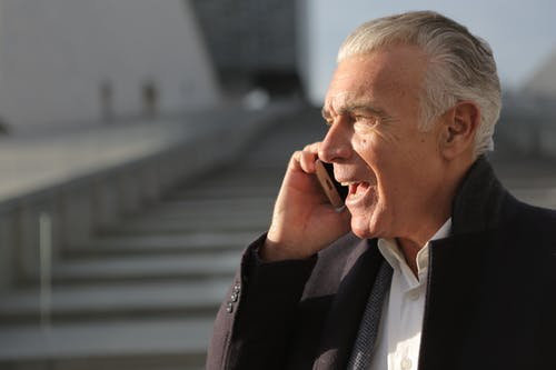 Man in Black Jacket Talking on Phone