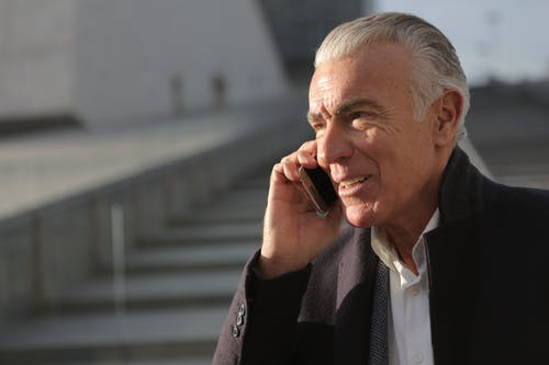 Man in Black Suit Jacket Talking on Phone