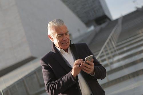 Homme En Veste De Costume Noir Tenant Un Smartphone