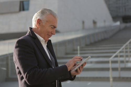 Man in Black Suit Jacket Holding White Smartphone