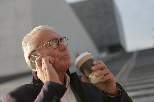 Man Using Smartphone While Holding Disposable Cup