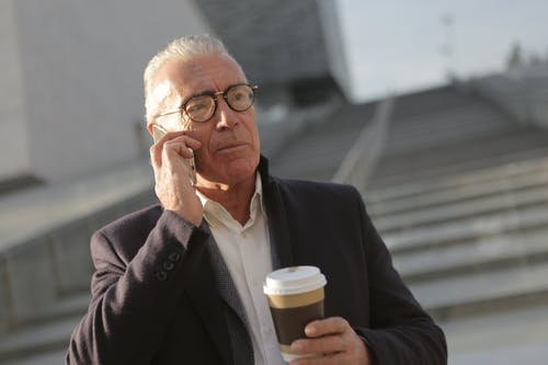 Man in Black Suit Jacket Holding Disposable Cup