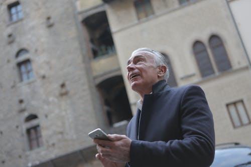 Elegant senior man browsing smartphone on city street