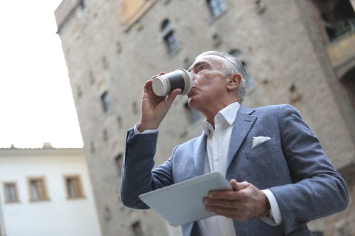 Man in Blue Suit Jacket Drinking from White Coffee Cup