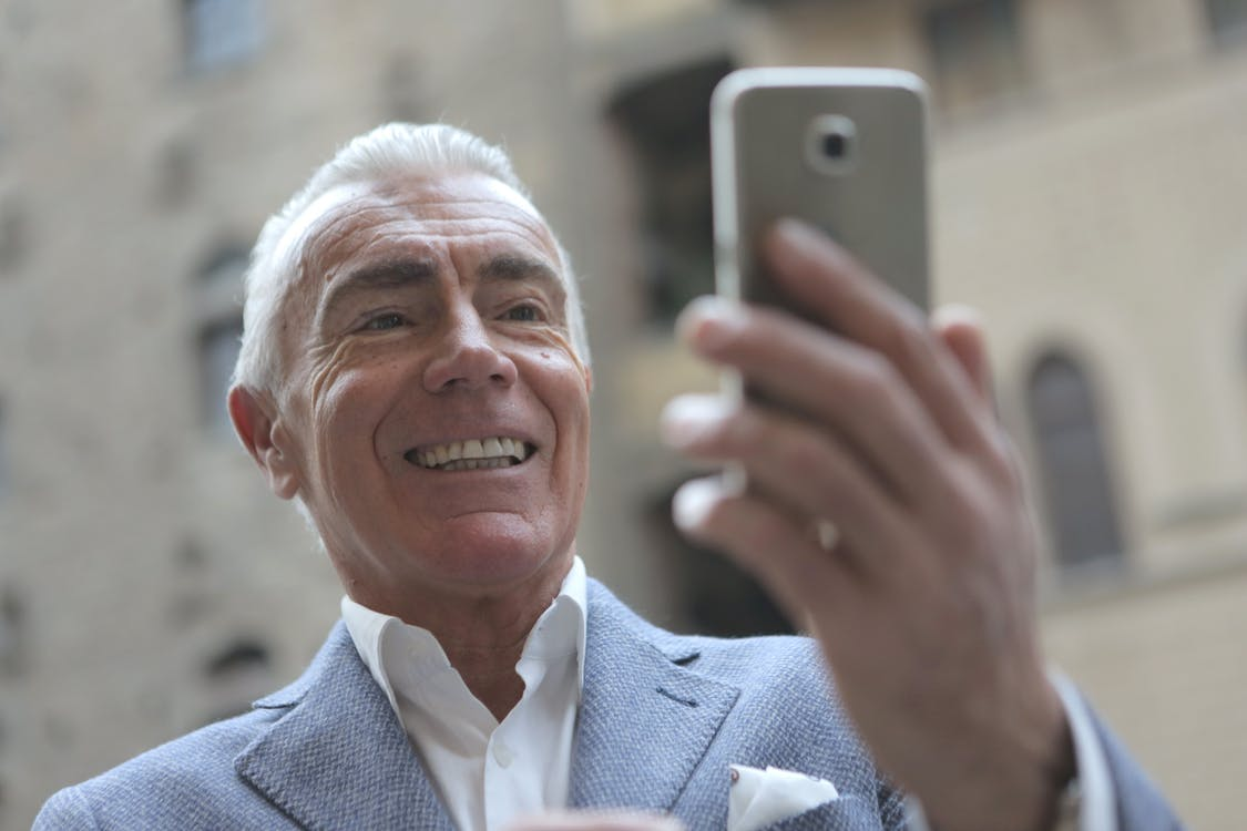 Man in Gray Suit Jacket Holding Smartphone