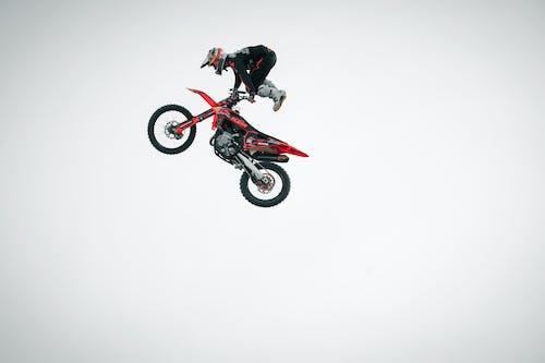 Man in Black and Red Motocross Suit Riding Motocross Dirt Bike