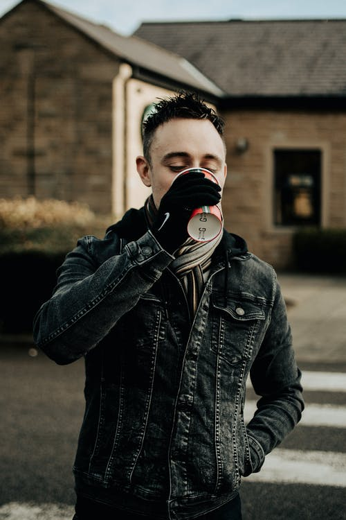 Man in Black Leather Jacket Drinking from White and Red Disposable Cup