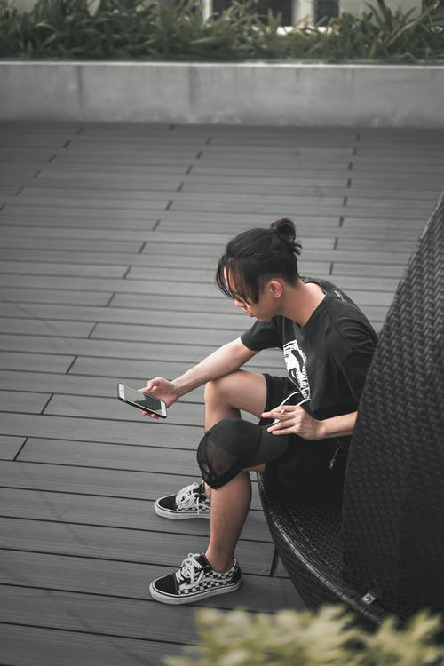 Unrecognizable ethnic man surfing internet on smartphone while smoking cigarette