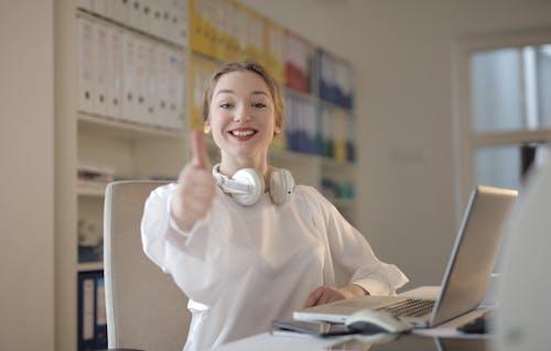 親指を立てながら白いトップを着ている女性