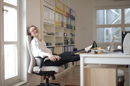 Woman in White Dress Shirt and Black Pants Sitting on Black Office Rolling Chair