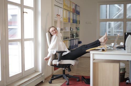 Dreamy female employee relaxing with feet on table in office