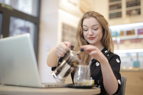Charming woman pouring tea into glass cup in cafe