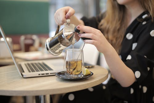 Woman pouring hot tea from french press into glass cup