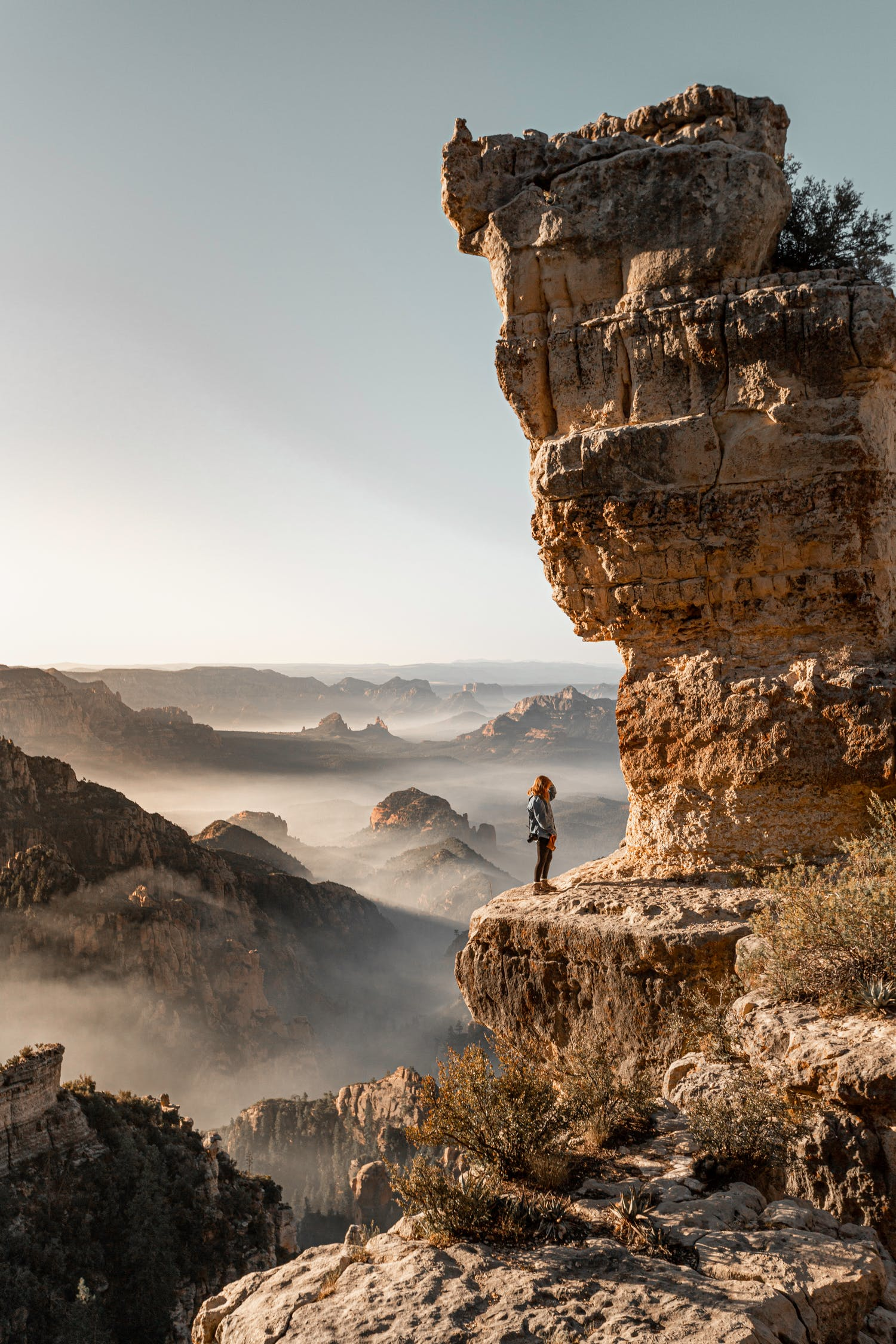 Side view of anonymous female traveler standing on shabby mount under high shapeless cliff under serene sky on foggy weather during trip