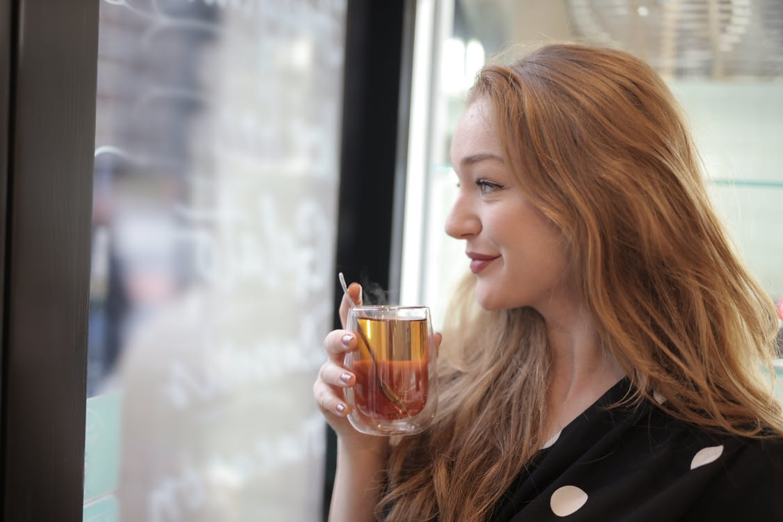 Satisfied woman enjoying tea in cafe