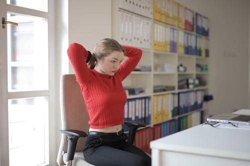 Female employee tying hair in office