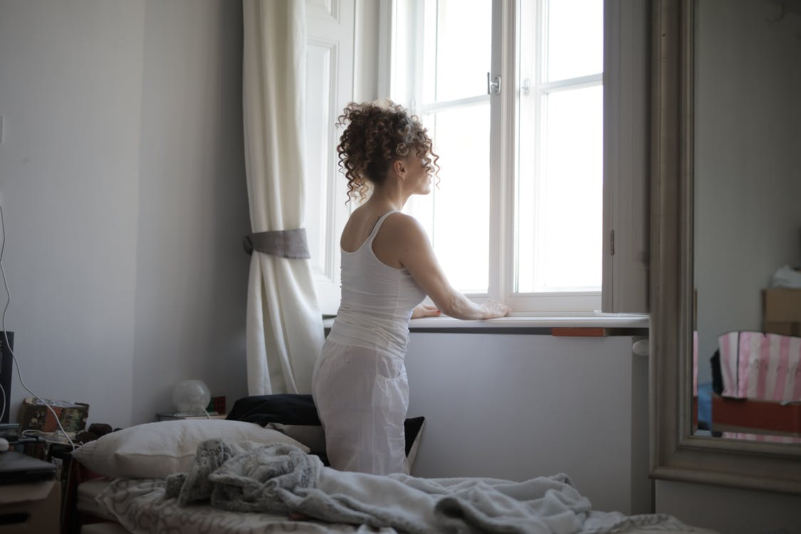 Calm woman in sleepwear on bed at home
