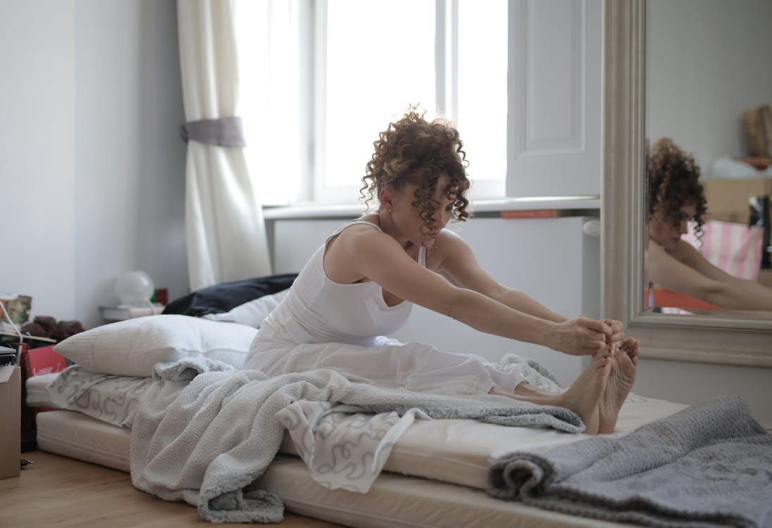 Woman in White Tank Top Sitting on Bed