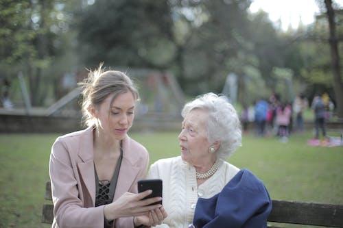 教資深母親的成年女兒在公園使用智能手機