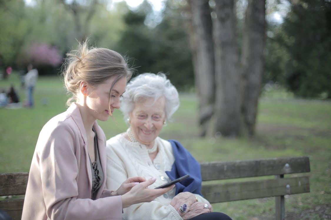 Daughter explaining elderly mother how using smartphone