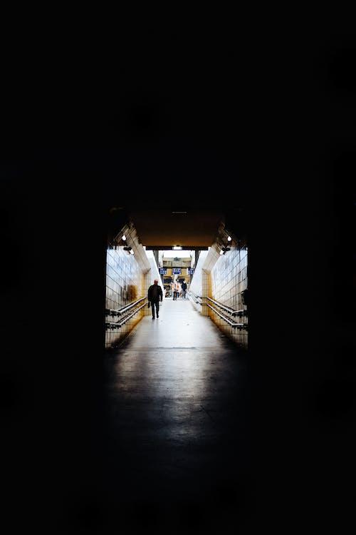 Photo of Person Walking in Dark Tunnel