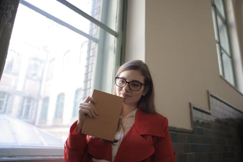 Woman in Red Blazer Holding Brown Book