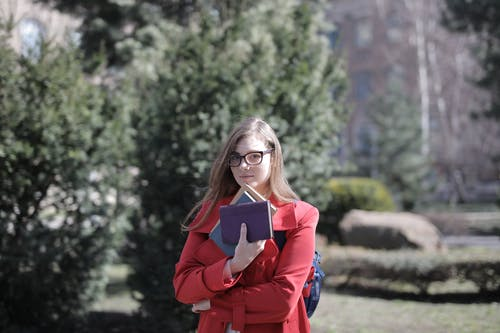 Woman in Red Coat Holding Books