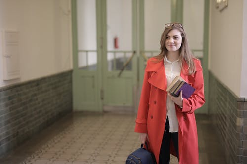 Smart female student with books and backpack in university hallway
