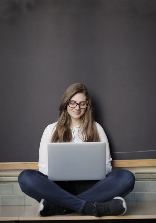 Woman in White Long Sleeve Shirt and Blue Denim Jeans While Using Macbook