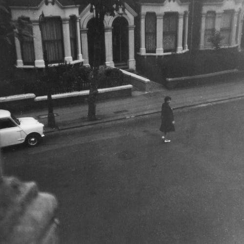 Grayscale Photo of Woman Walking on Street