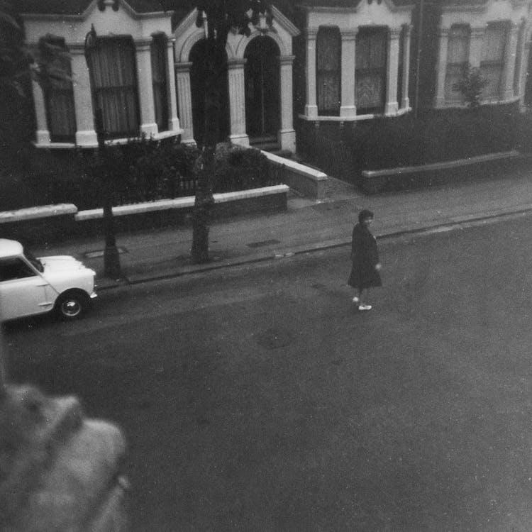 Grayscale Photo of Woman Walking on Street