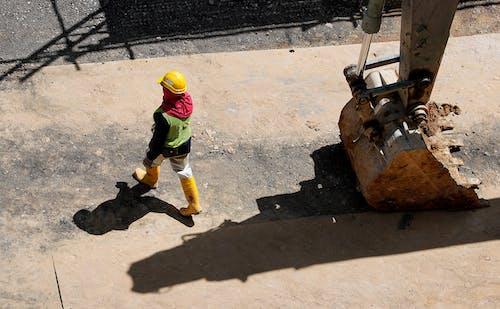 Фотография человека, идущего рядом с обратной лопатой, под высоким углом