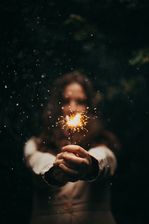 Person Holding Lighted Sparkler during Nighttime