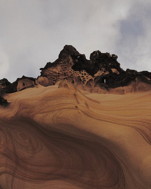 Rocky formations on sandy terrain in desert under cloudy sky