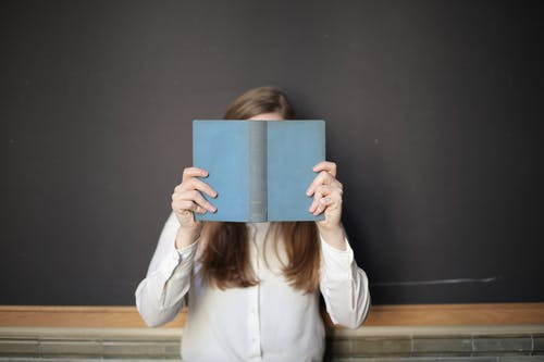 Woman in White Long Sleeve Shirt Holding Blue Book