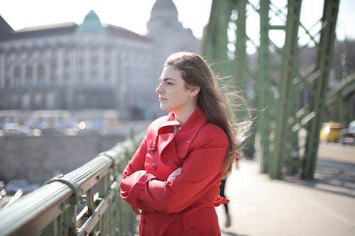 Woman in Red Coat Standing Near Metal Railing