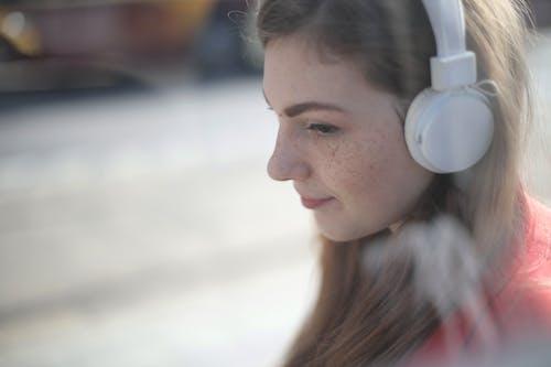 Woman Listening to Music Using White Headphones