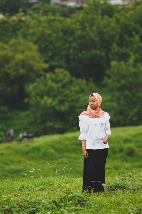 Woman in White Long Sleeve Shirt and Black Pants Standing on Grass Field
