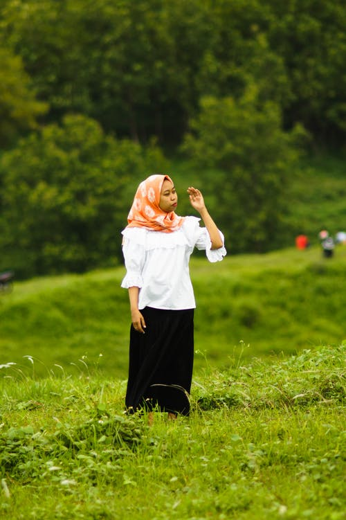 Woman in White Long Sleeves and Black Pants Standing on Grass Field