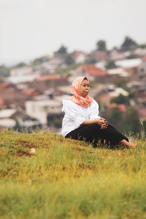 Woman in Orange Hijab Sitting on Grass Field